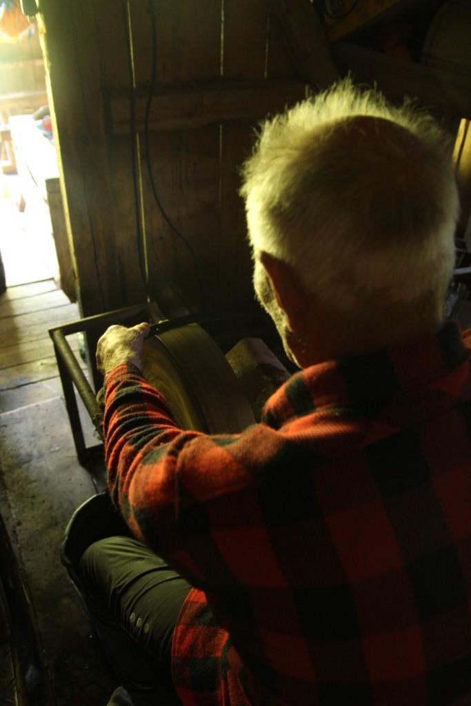 Olav har en eldriven slipsten. Han sitter på en pall med raka armar. Han har kontroll. Han vet vad han gör.