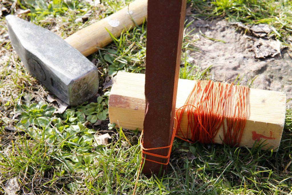 Använd en märklina och två pinnar (som slås ner i marken) så att häcken blir rak.