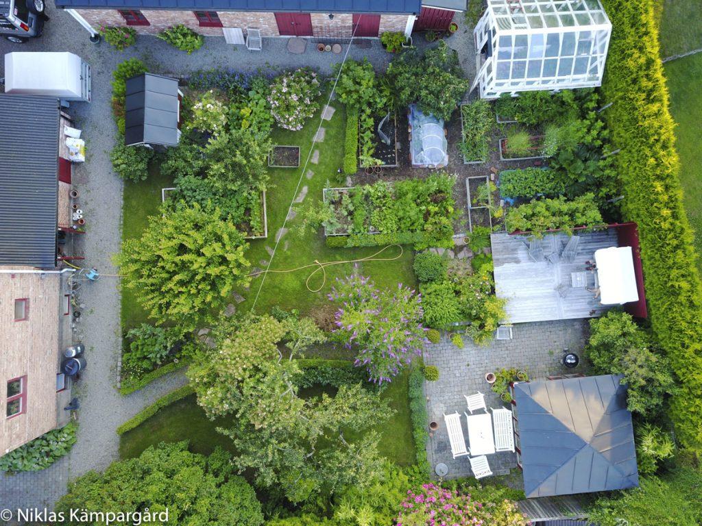 Med vedboden på ena sidan gräsmattan och huset på den andra är det smidigt att använda Ölandssten på gångarna.
