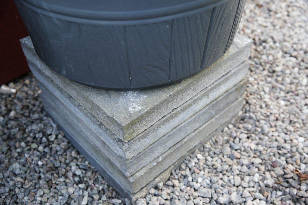 Placera tunnan på ett gäng betongplattor (eller köp en fot i plast) så att man enkelt kan tappa vatten rakt ner i vattenkannan.