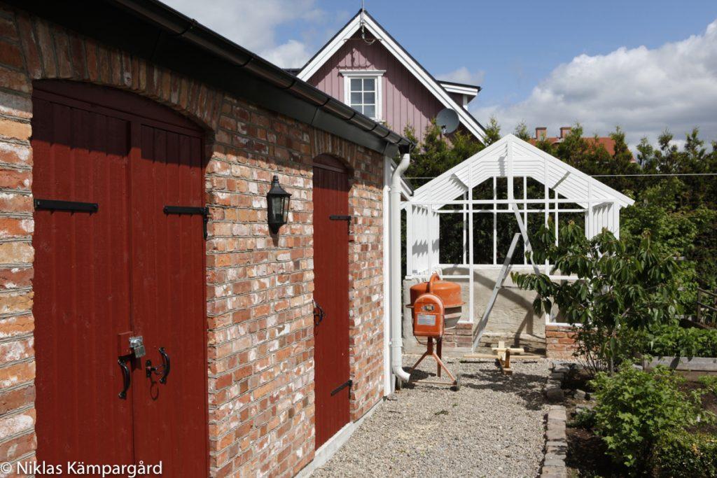 För att smälta in i miljön närmast uthuset valde vi att bygga ett växthus av trä, tegel och gamla fönster.