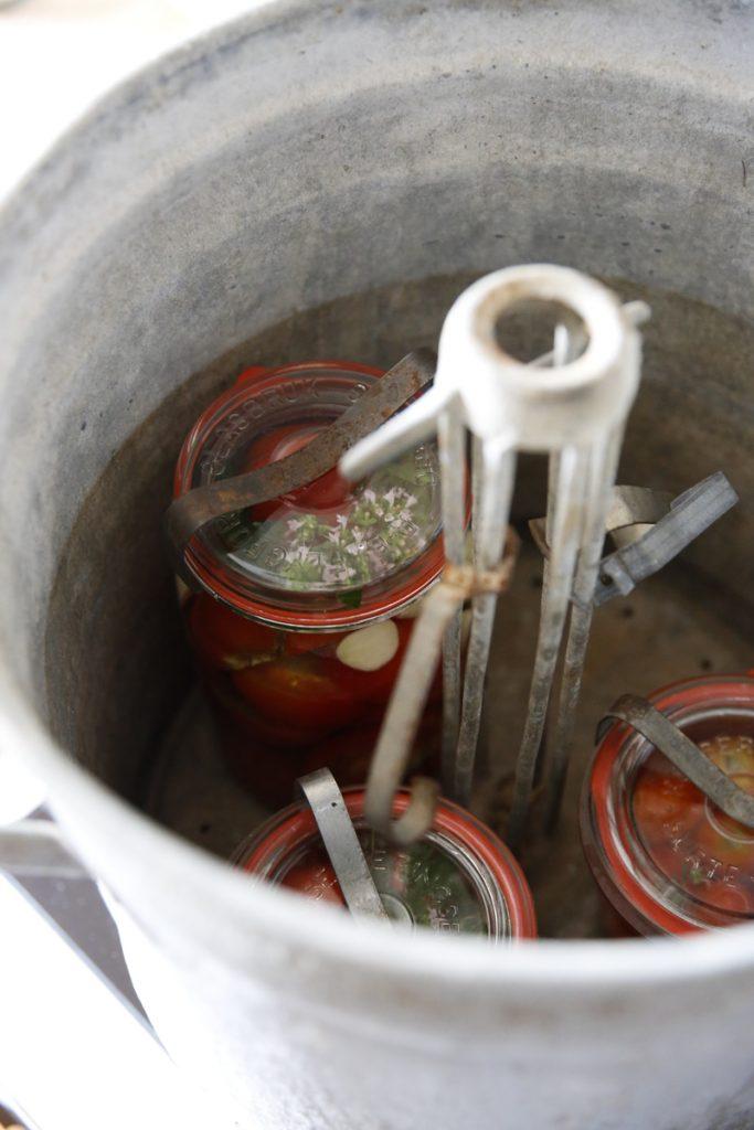 Konserveringsapparaten består av en helt vanlig gryta med lock och metalltappar som håller burkarna på plats.