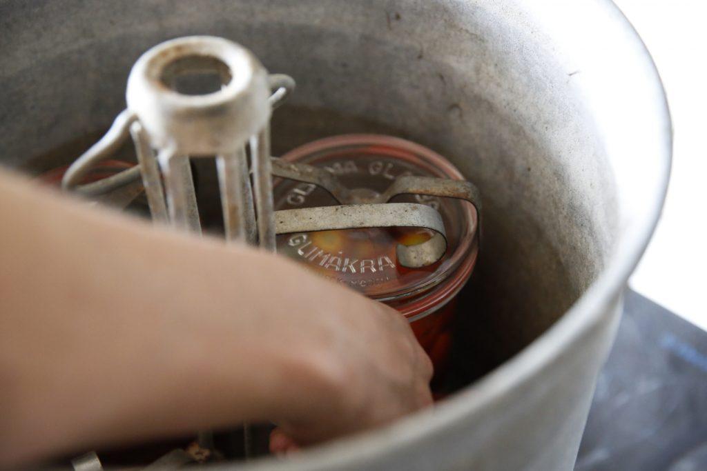 Hala ner burkarna i konserveringsapparaten och fäst dem i stativet.