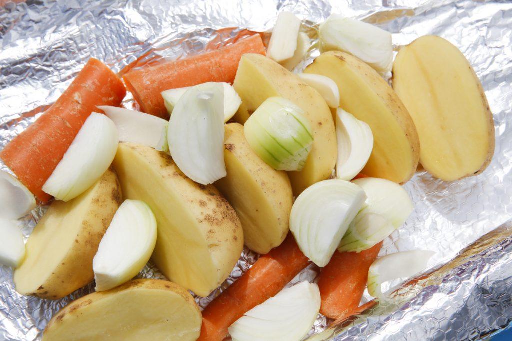 Potatis, lök och morötter blir ljuvligt gott i marken. Glöm inte att krydda.