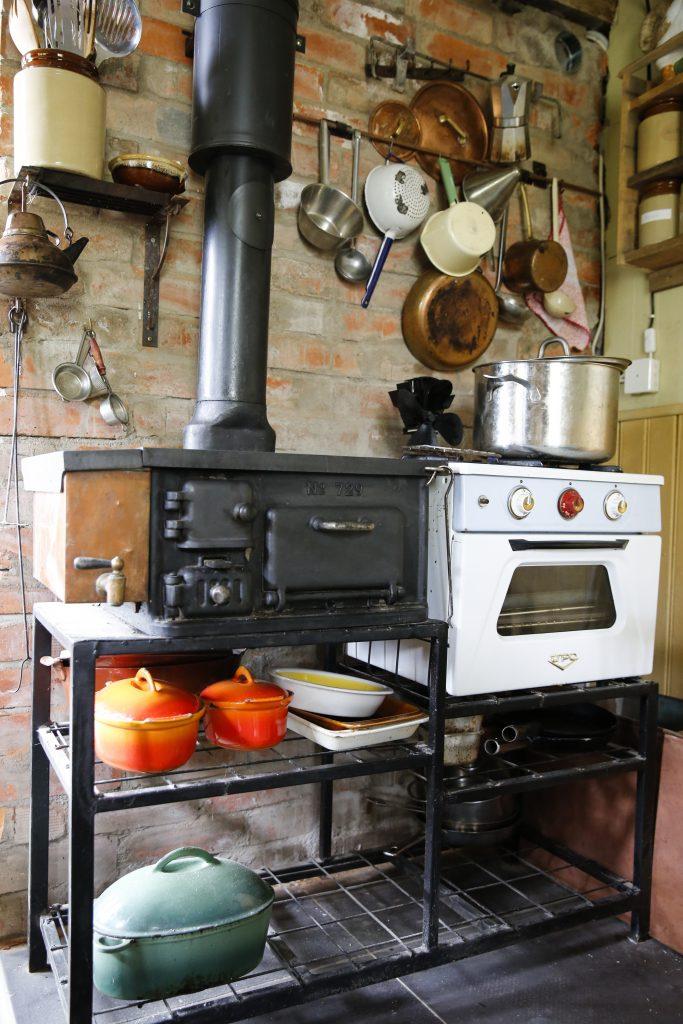 Även en klassisk vedspis (i köket) ger bra möjligheter att värma upp ett rum och samtidigt laga mat.