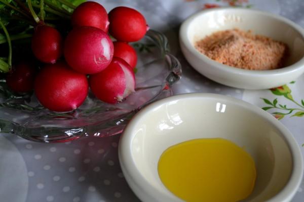 Rädisor på ett fat bredvid andra fat med en skvätt olja och örtsalt.