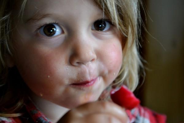 En liten tjej äter rädisor.