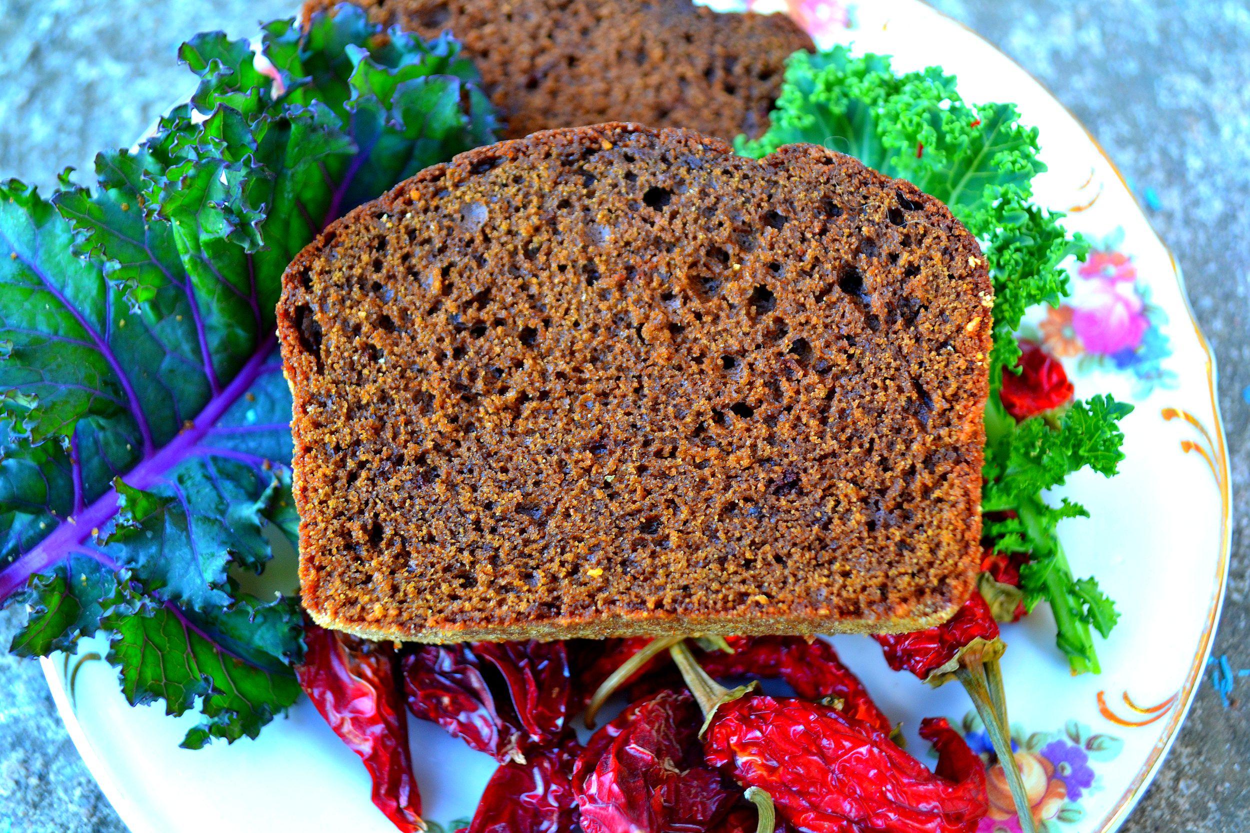 Mörk chokladkaka på ett fat tillsammans med grönkål och chilifrukter.