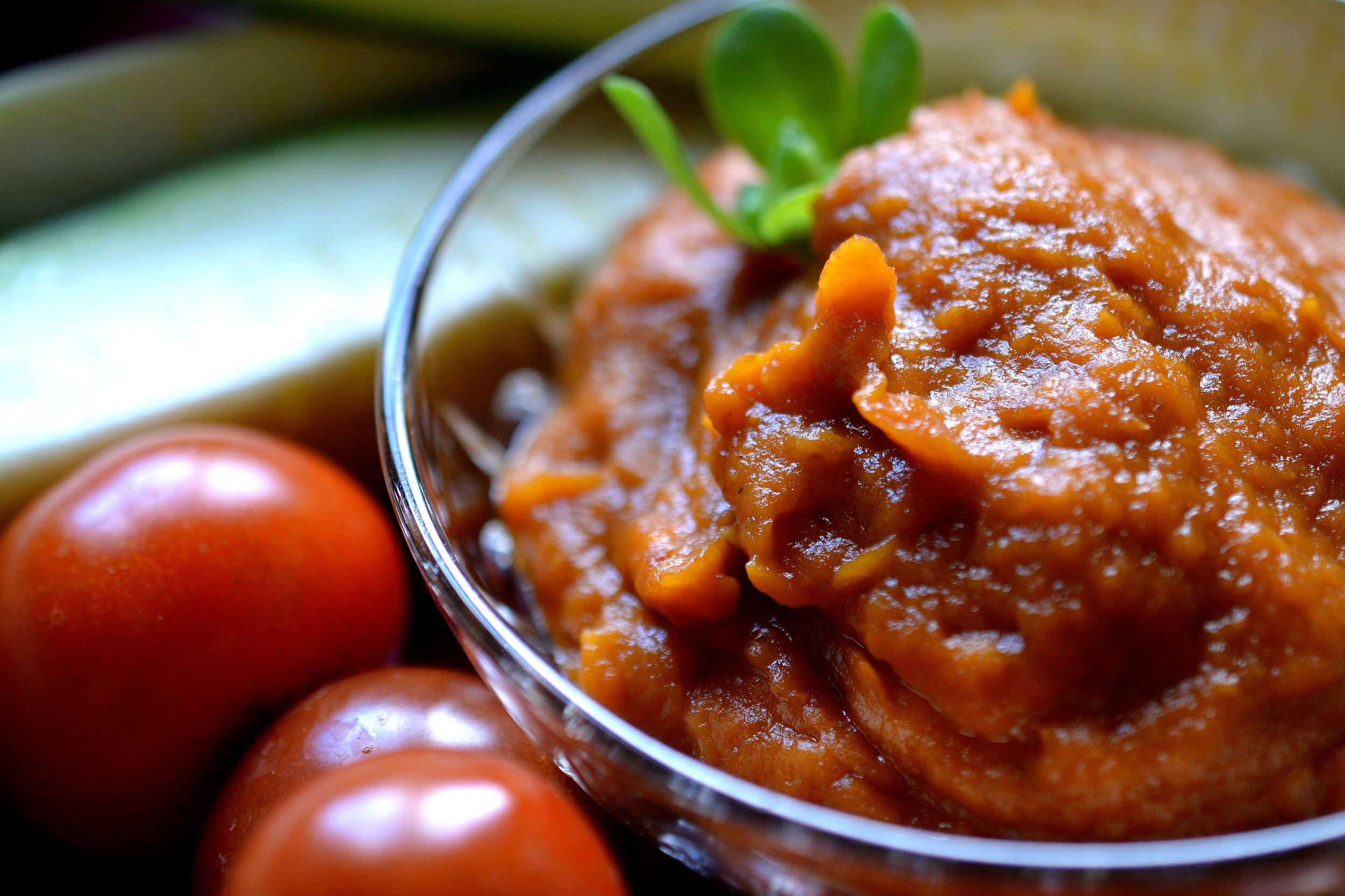 En tegelfärgad röra ligger i en liten glasskål, omgiven av tomat och squash.