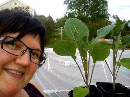 Agneta tittar fram bredvid två små kålplantor i kruka.