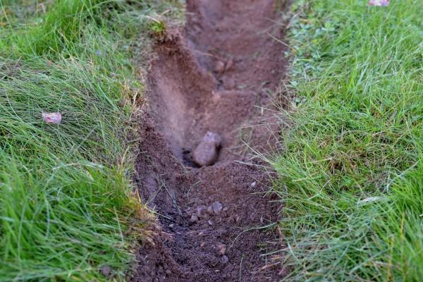 Ett litet grävt dike i gräsmattan.