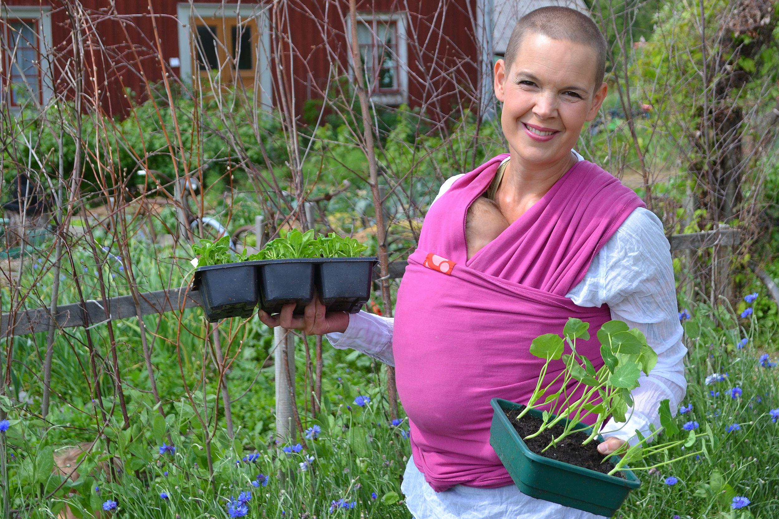 Sara bär på odlingstråg i köksträdgården