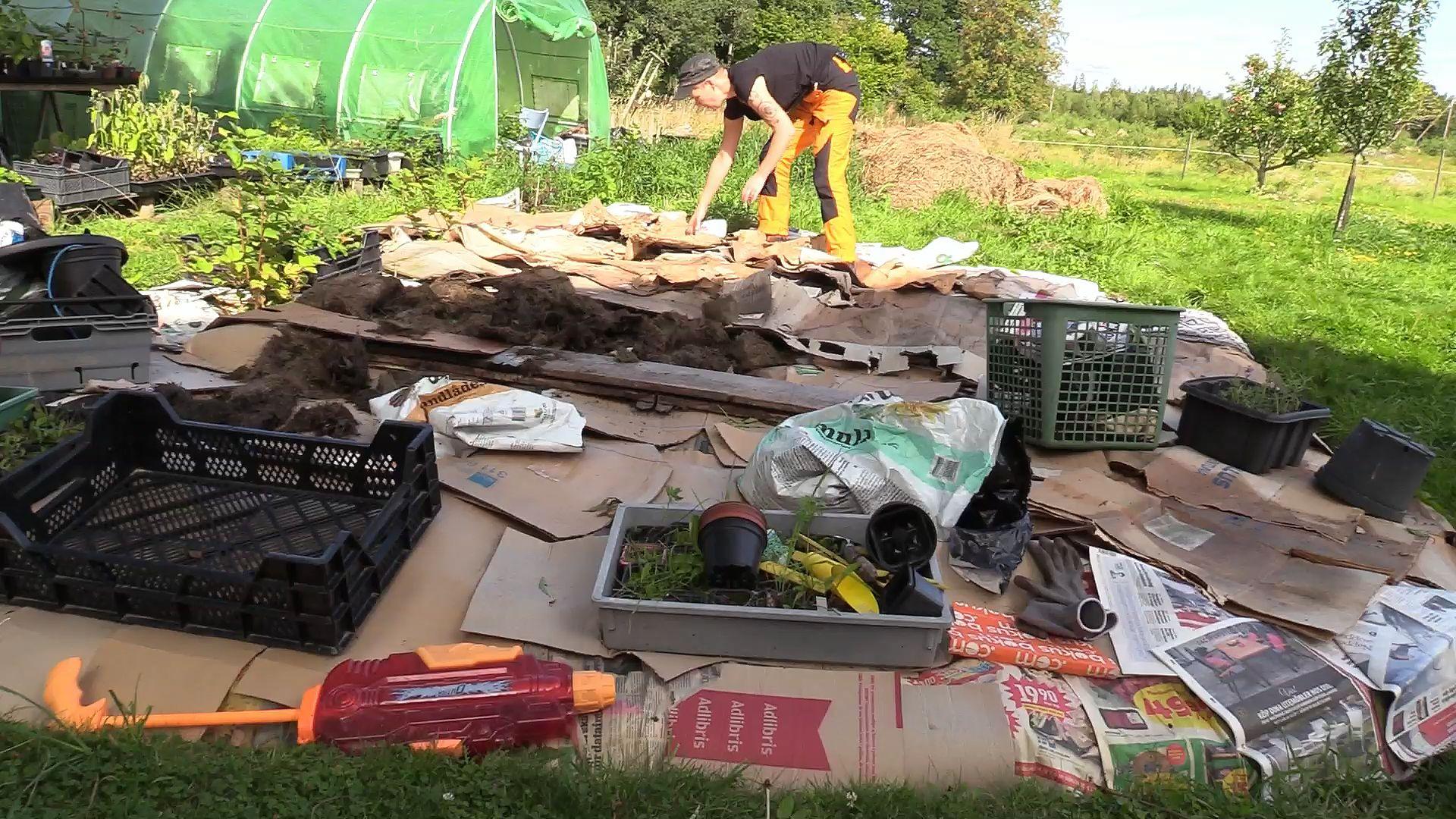 Sara lägger kartonger på marken.