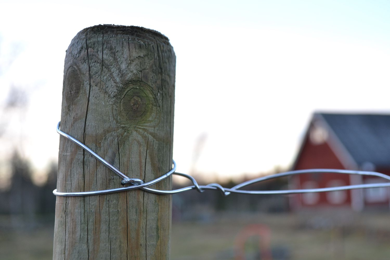 En stolpe med ståltråd i motljus.