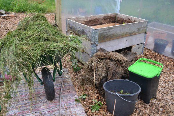 Olika material till komposten, ensilage, gräsklipp.