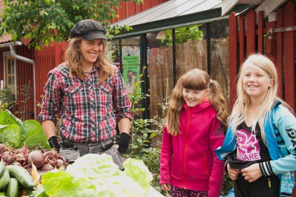 Maja och två barn vid ett bord grönsaker.