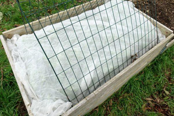 En pallkrage täckt med kompostgaller och fiberduk.